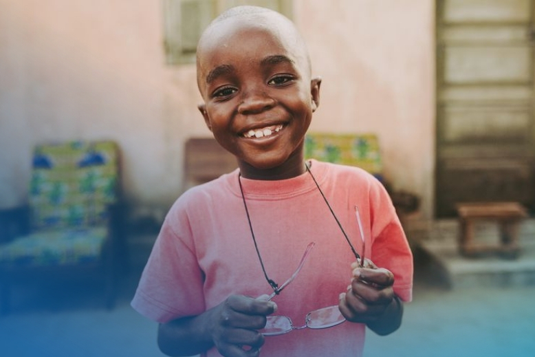 Benissan, a sponsored child from Togo, holds his glasses on a string around his neck while standing outside his home. Smiling to camera, close-up.