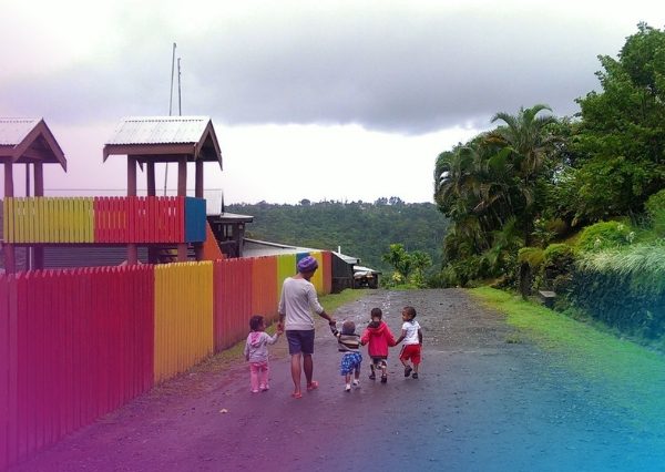 Photo from Homes of Hope Fiji, a woman and four children walk down the road beside a playground happily holding hands.