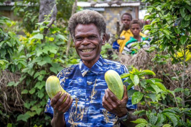 A-man-proudly-holds-two-cucumbers-he-has-grown-in-Vanuatu.jpg