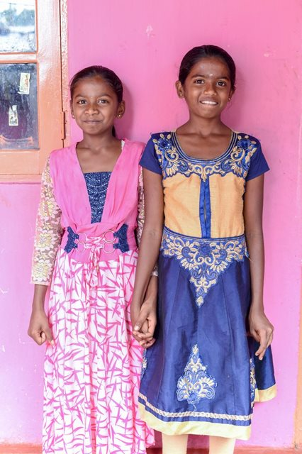 Inseparable sisters Rizwani and Krishanthini smile and hold hands outside their cheerful pink house.