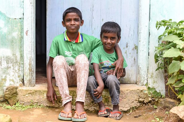 Idhaya and his little brother Ajit sit arm-in-arm on the front-step of their home