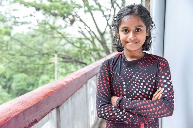 Jasmitha stands with her arms folded, standing up, shyly smiling to the camera