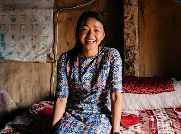 A young Nepali adult laughs to the camera while sitting inside her home