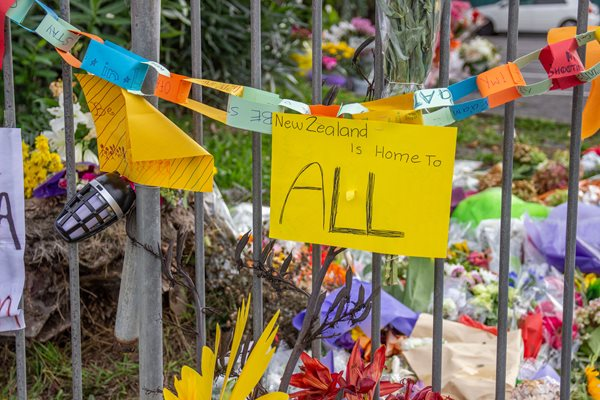 "A sign outside a mosque flower tribute on March 19, 2019, Auckland reads, ""New Zealand is home to ALL."" In remembrance of those killed in the Christchurch mosque terror attacks."