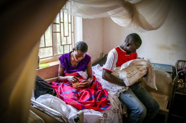Juliet rests a moment while her husband, Edward, says his first hello to their first-born child, Christine in a public hospital in Uganda.