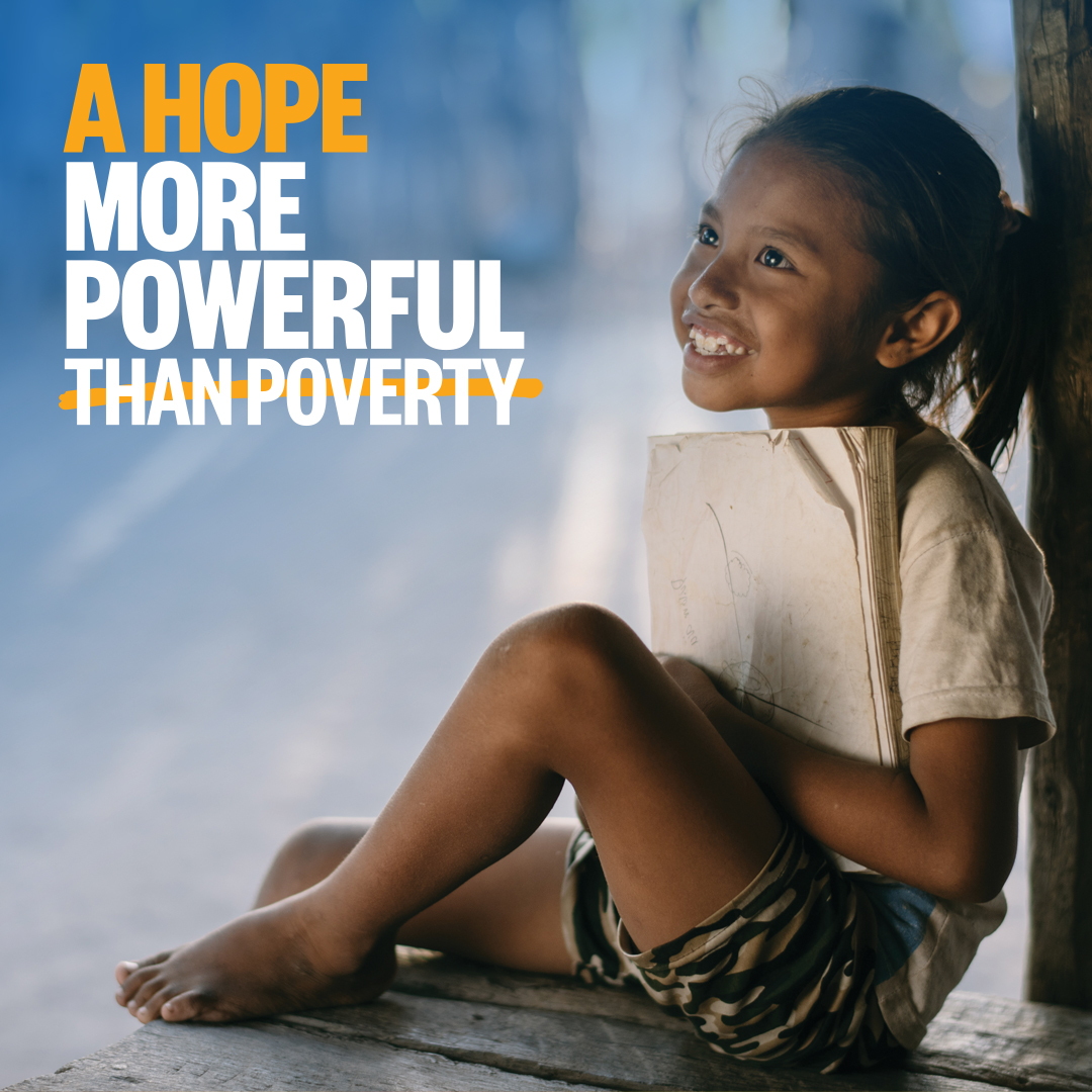Child Sponsorship, A girl from the Philippines smiles while she sits holding her school book.