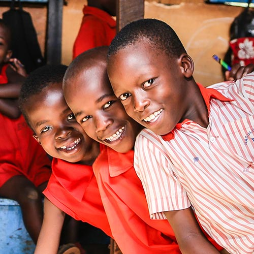 Child Sponsorship, Three boys from Uganda, smiling, sitting at desks in a classroom